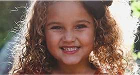 little girl with curly hair smiling