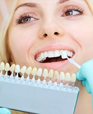woman checking veneers against smile