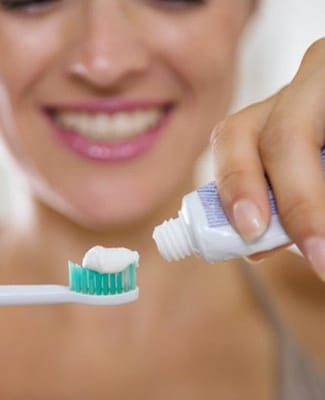 A woman applying toothpaste to an electric toothbrush