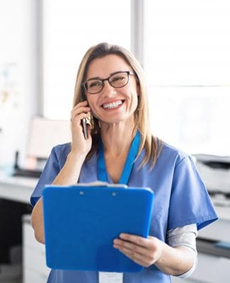 dental assistant talking on phone and holding blue clipboard