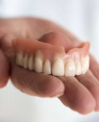 hand holding top denture