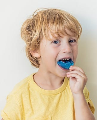 boy putting in blue mouthguard