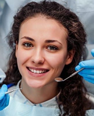 young woman with curly hair smiling in the dental chair