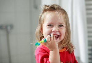 little girl smiling with a toothbrush
