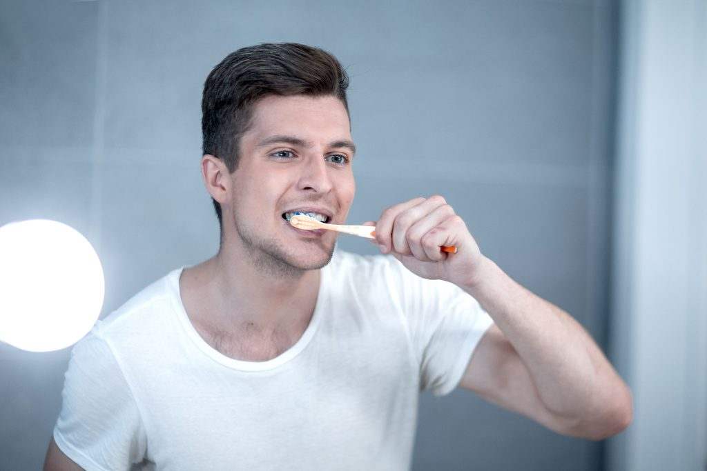 Young man uses a toothbrush to keep his teeth clean and healthy.