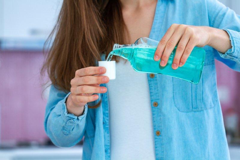 Woman pouring mouthwash into cap